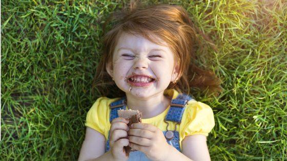 Lachendes Kind liegend im Gras