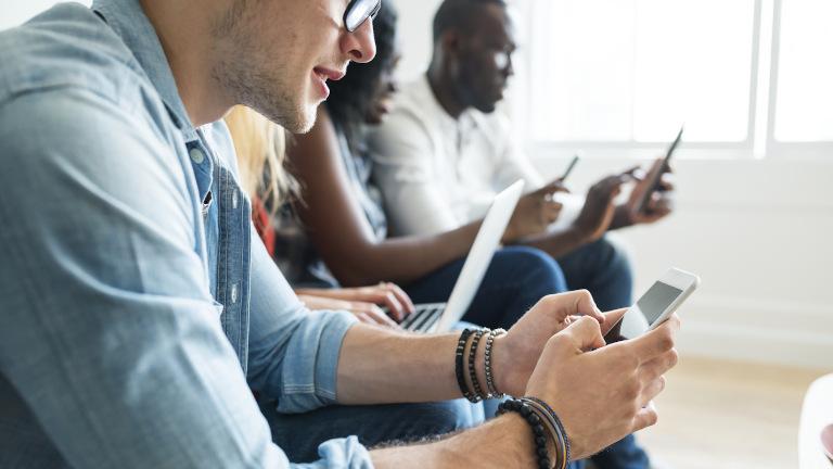 Mehrere Leute surfen auf Smartphones und Laptops im WLAN