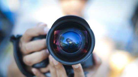 In einem Kamera Objektiv spiegelt sich eine Landschaft