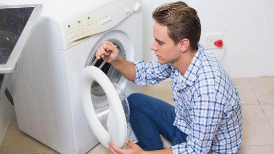 Junger Mann beim Waschmaschine anschließen