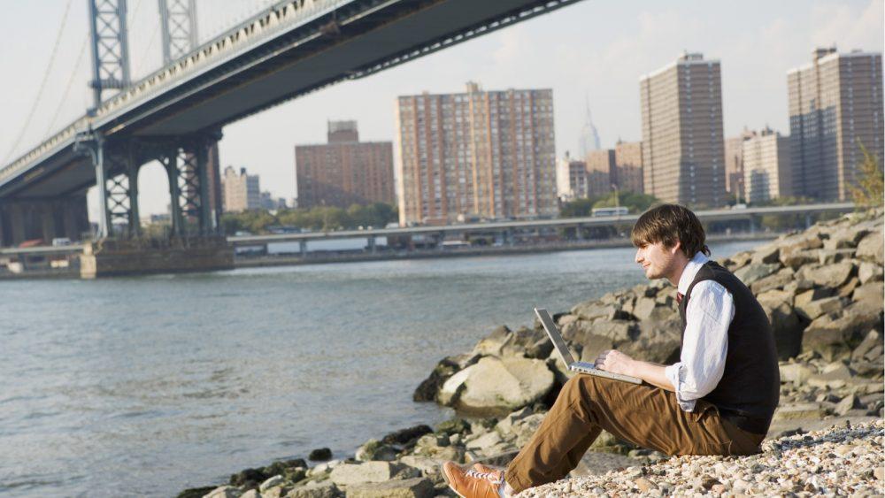 Ein Mann sitzt mit einem Laptop am steinigen Ufer unter der Brücke und blickt in die Ferne
