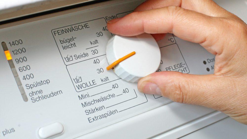 Hand stellt Waschmaschinenregler um