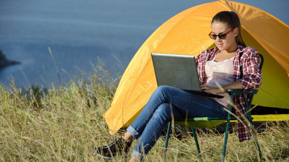 Junge Frau surft per Laptop beim Camping am Meer