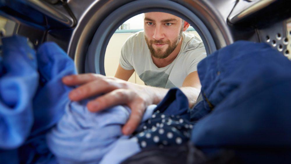 Mann gibt verschiedene blaue Kleidungsstücke in die Waschtrommel