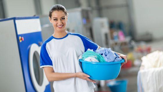 Frau mit Wäschekorb und frisch gewaschener Wäsche