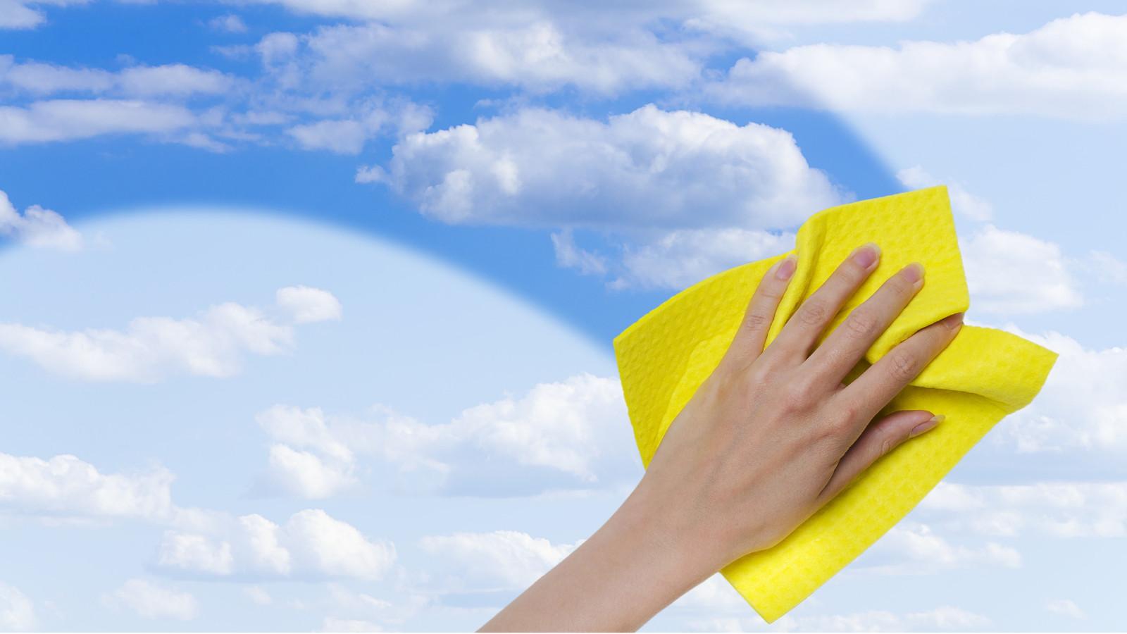 Hand wischt mit Putztuch Scheibe frei