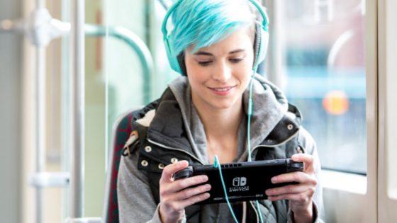 Mädchen spielt mit Nintendo Switch im Bus