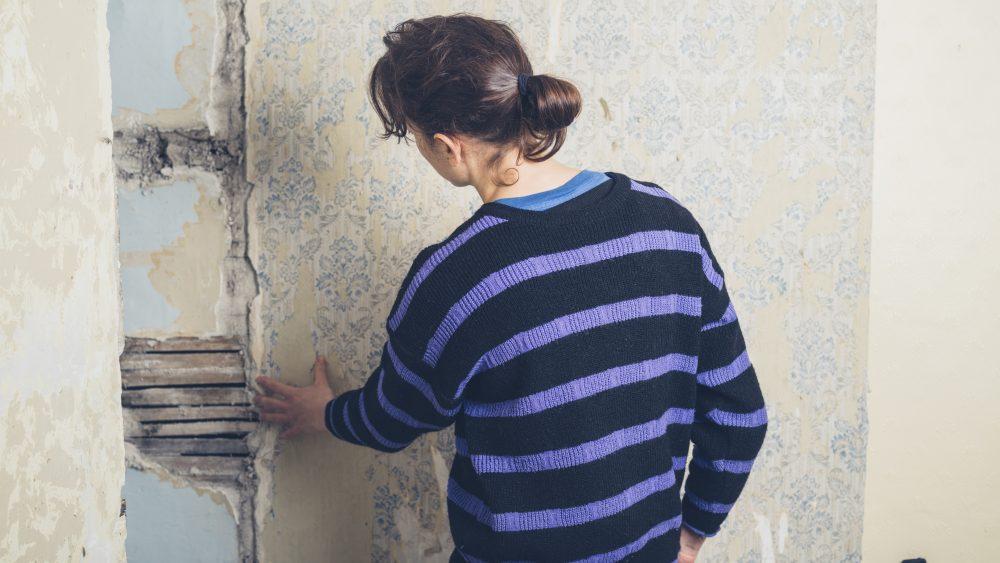 Wie stark ist der Schimmelbefall an der Wand? Um diese Frage zu klären, müssen Sie erst die Tapete entfernen. Denken Sie dabei an Handschuhe und Atemmaske.