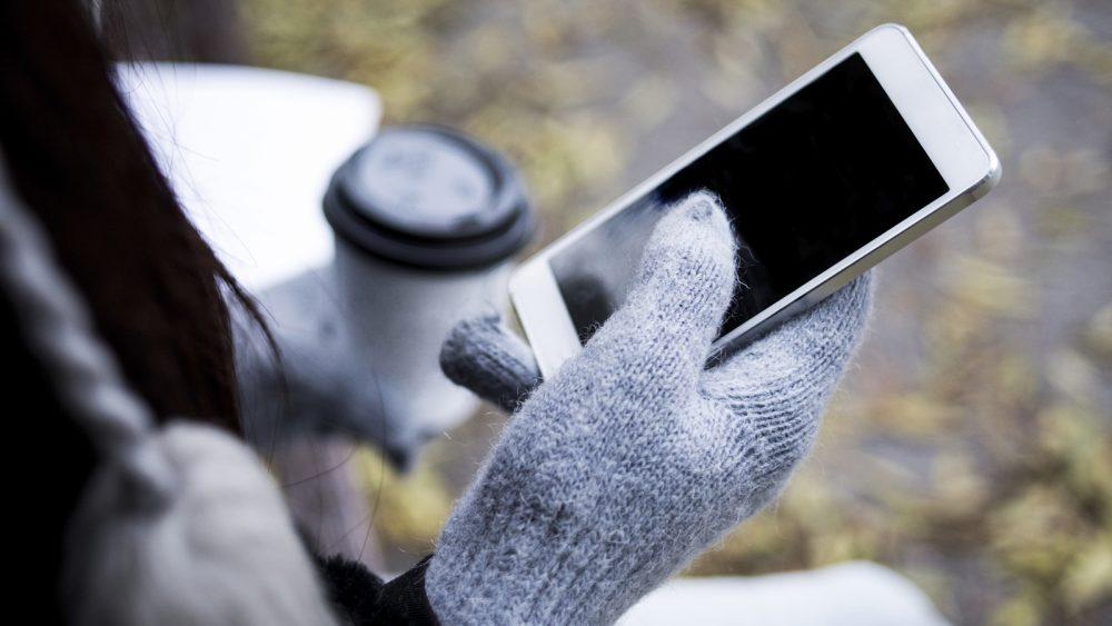 Eine Person mit Handschuhen hält ein Smartphone in der Hand.
