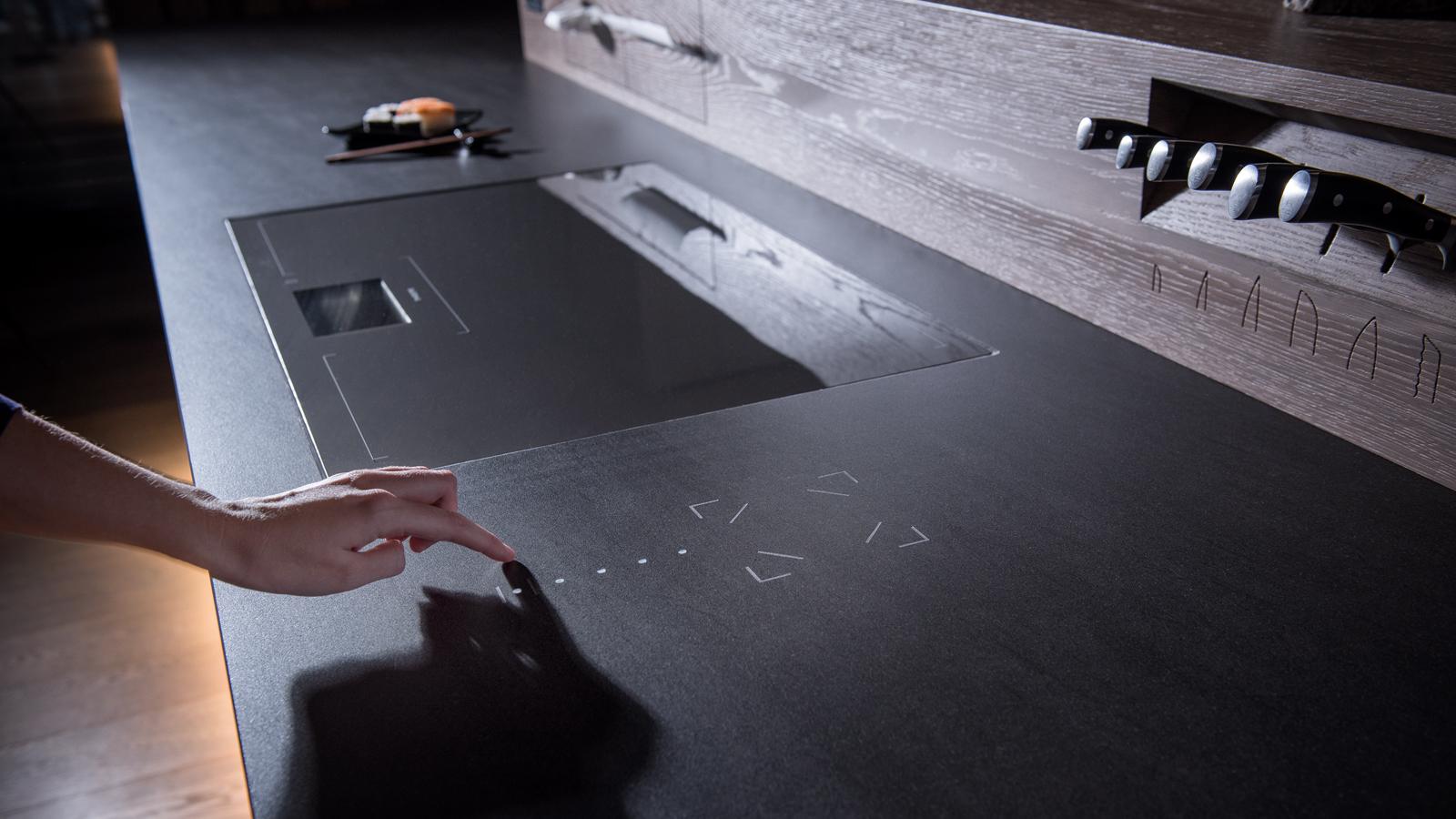 Durch Berührung des Natursteines an den eingravierten Stellen aktiviert der Anwender die Steuerung von Licht, Beschattung oder Musik.