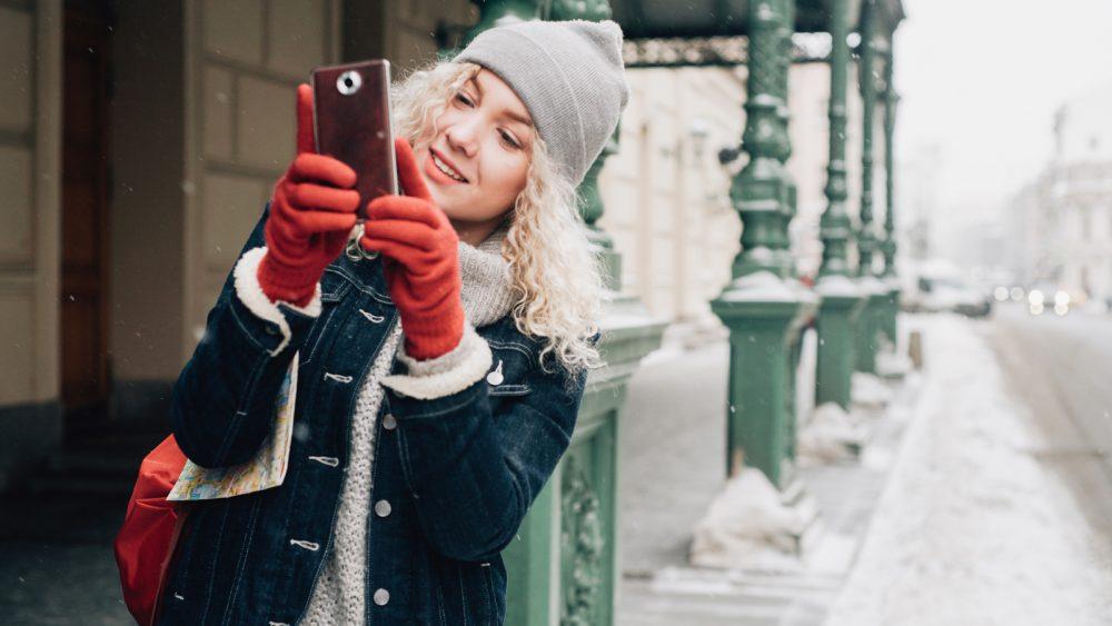 Eine Person ist im Winter draußen und macht mit dem Handy Fotos.nter draußen und macht mit dem Handy Fotos.
