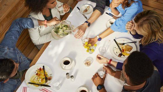 Gruppe von jungen Menschen bei gesunder Mahlzeit, alle mit Smartwatch am Arm