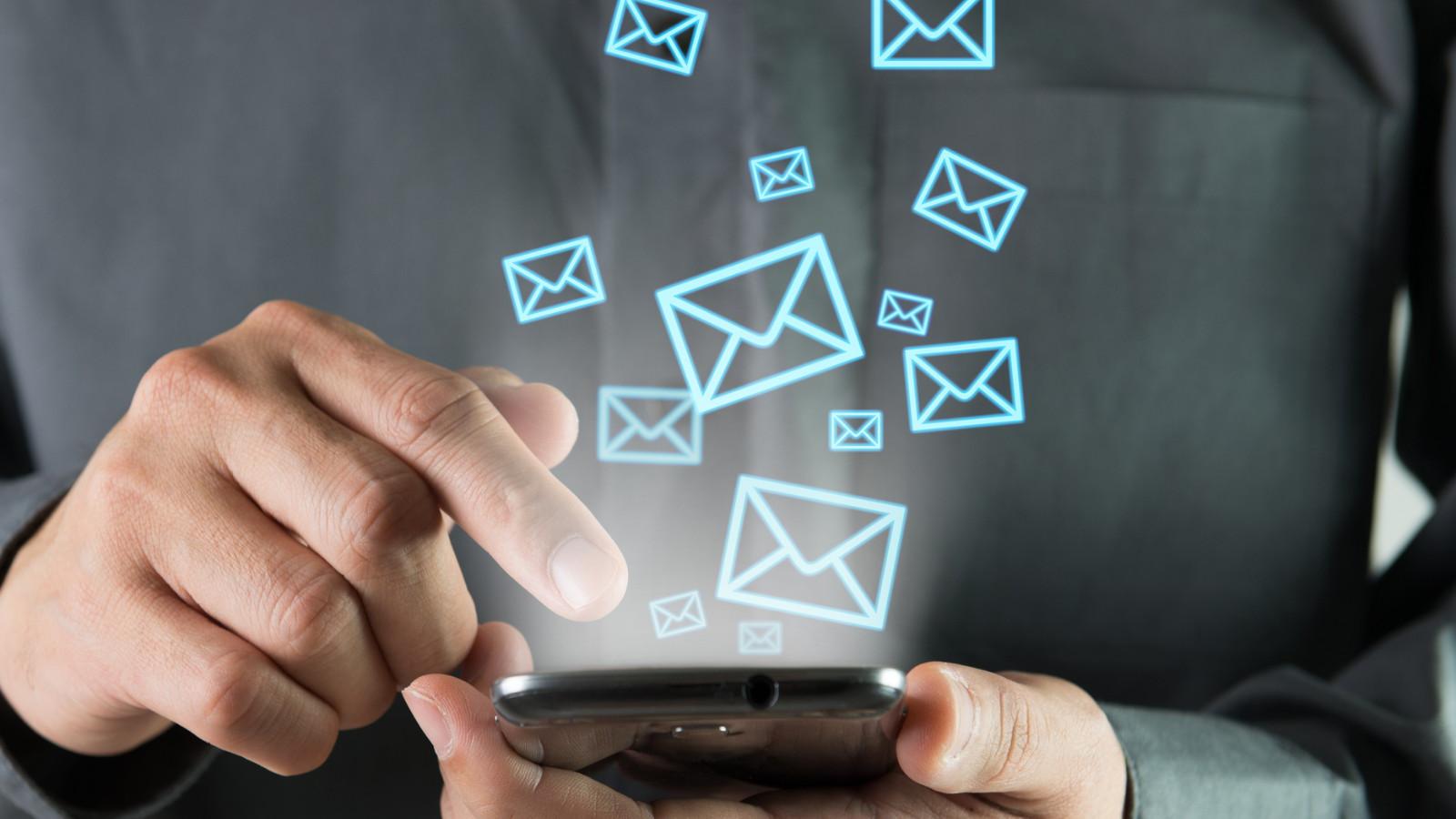 Mann tippt auf Handy und empfängt Mails