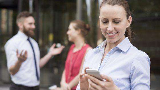 Frau guckt auf Smartphone, Kollegen stehen im Hintergrund