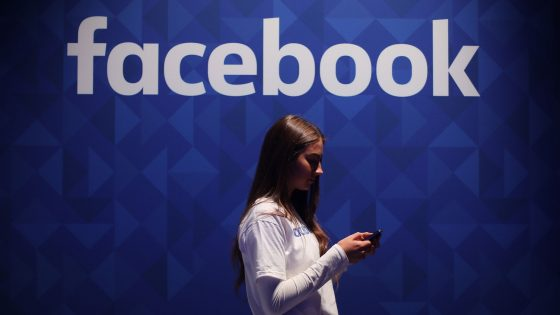 Junge Frau blickt auf Smartphone vor Wand mit Facebook-Schriftzug
