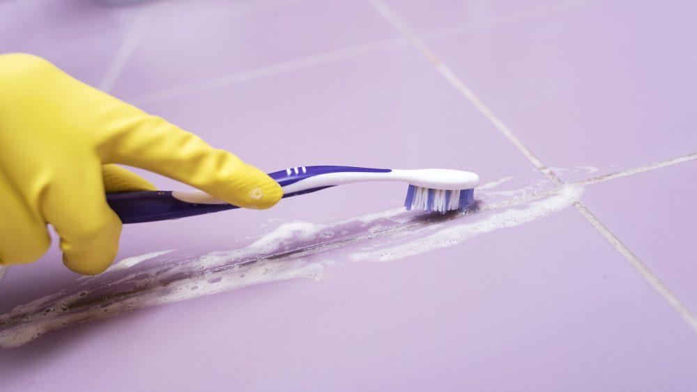 Mit einer Zahnbürste werden die Fliesenfugen gereinigt