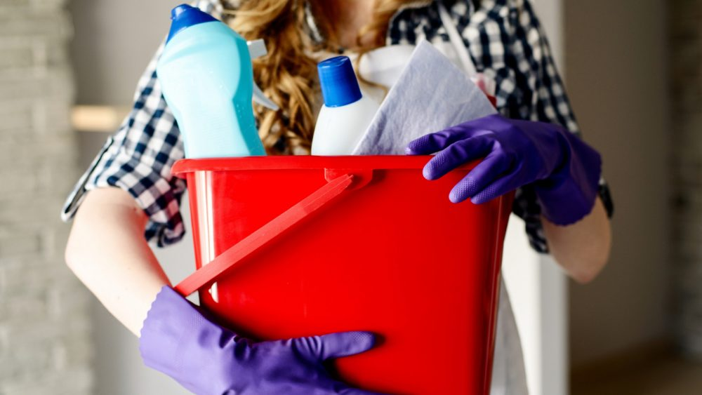 Frau hält Behälter mit drei Reinigern