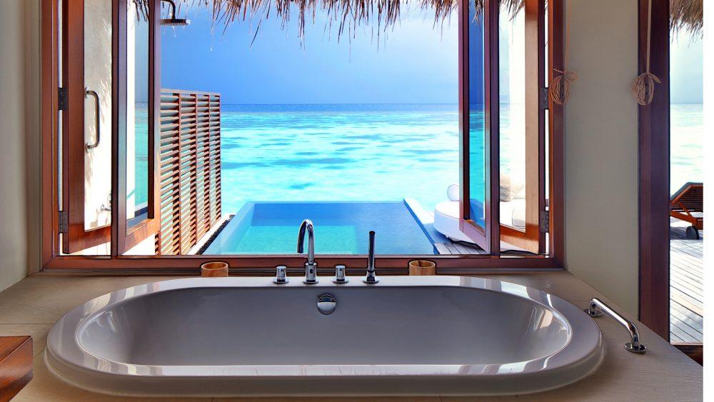 Badewanne vor einem großen Fenster mit Blick auf Pool und Meer