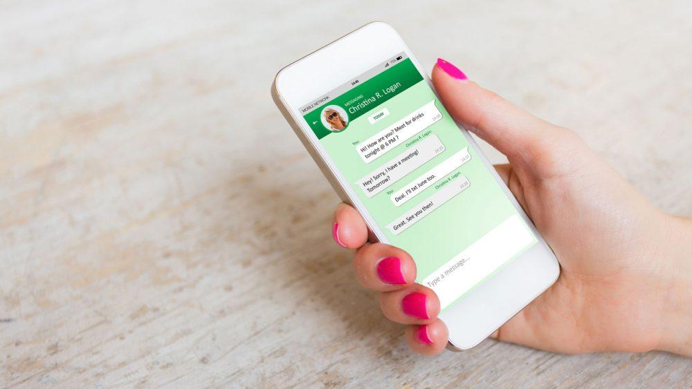 Frauenhand mit Smartphone und geöffnetem WhatsApp Messenger