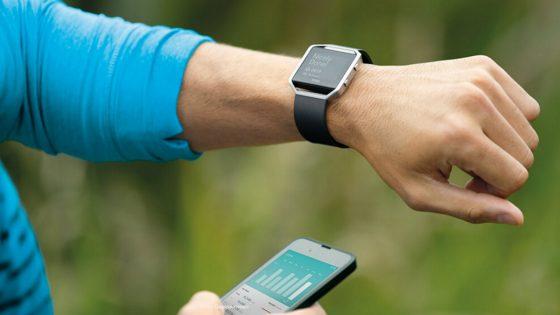 Sportler mit Fitnesstrecker und App auf Smartphone