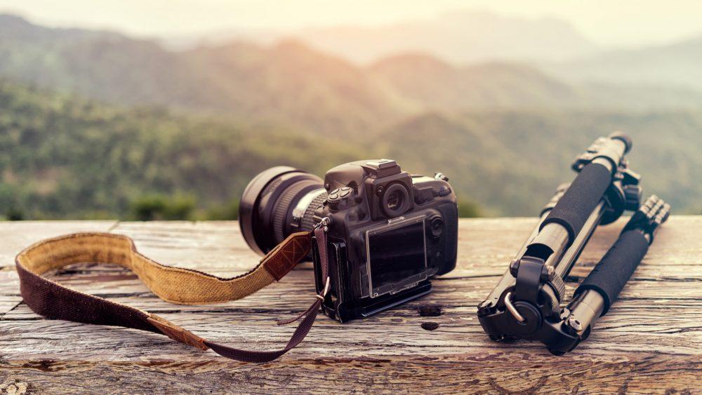 Kamera und Stativ vor Bergpanorama