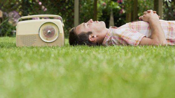 Mann hört DAB+ auf der Wiese mit einem Retro-Radio