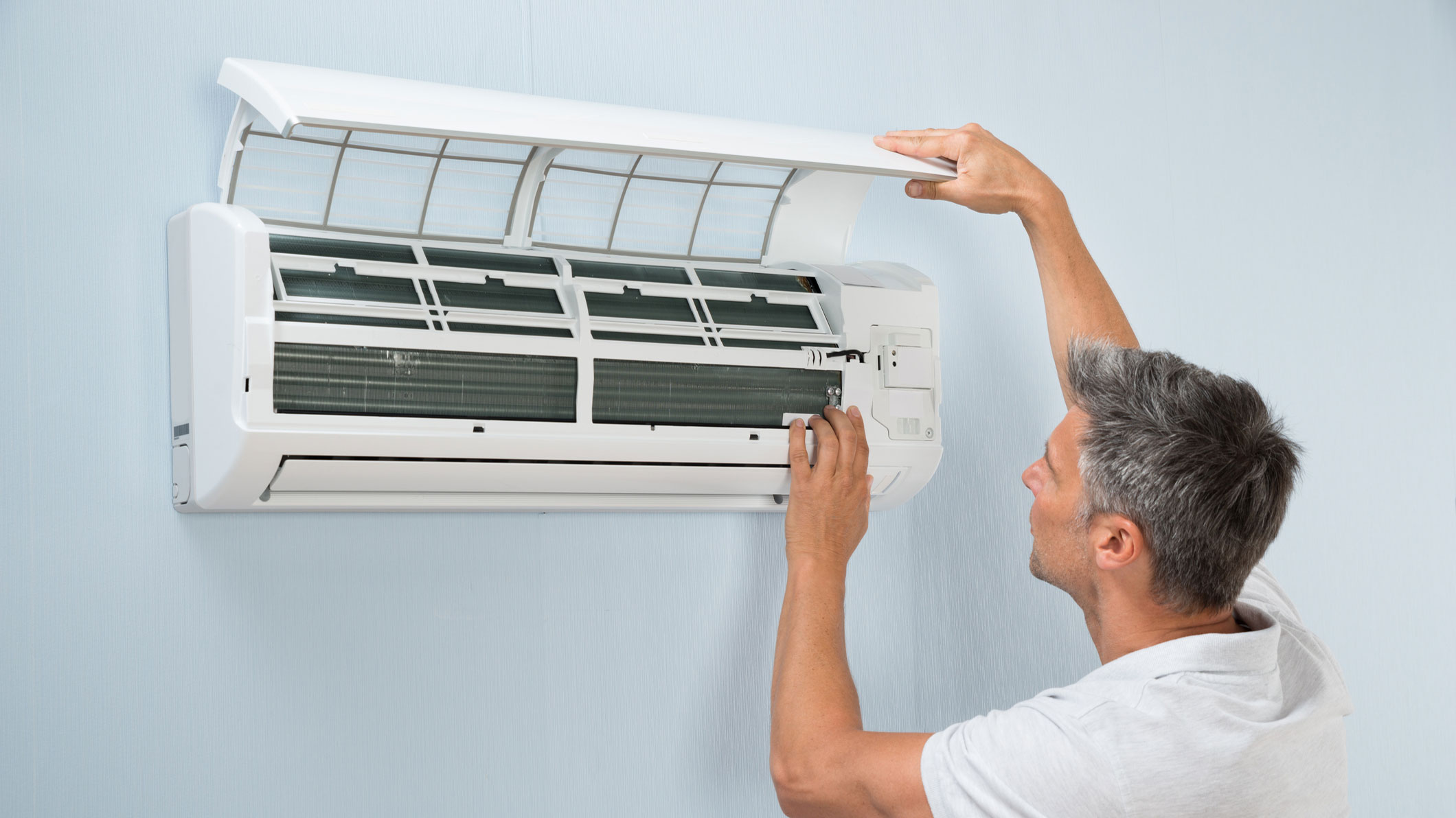 Ein Mann wartet seine Klimaanlage.