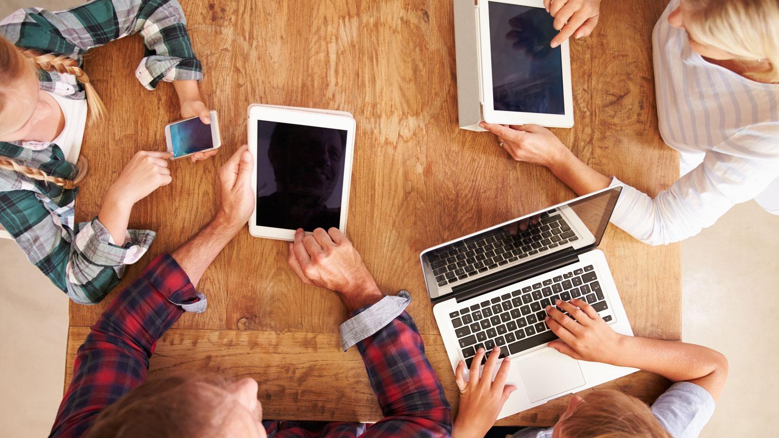 Familie mit Apple-Geräten am Tisch nutzt Apple-Familienfreigabe