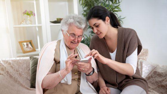 Eine junge Frau erklärt einer Seniorin ein iPhone