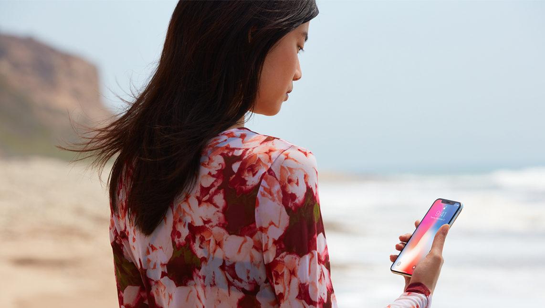 Frau am Strand mit iPhone X