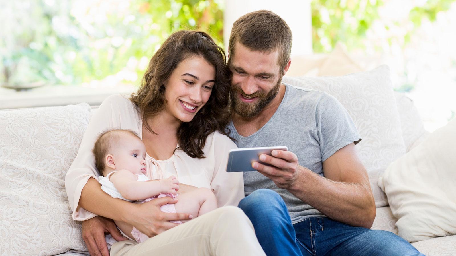 Eltern mit Kleinkind und Smartphone auf einem Sofa