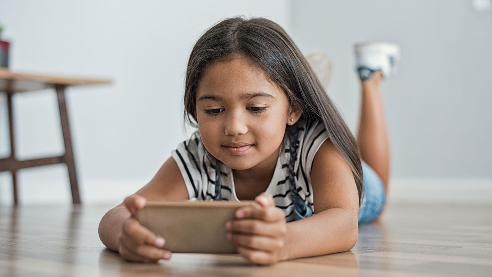 Kind schaut auf ein Smartphone