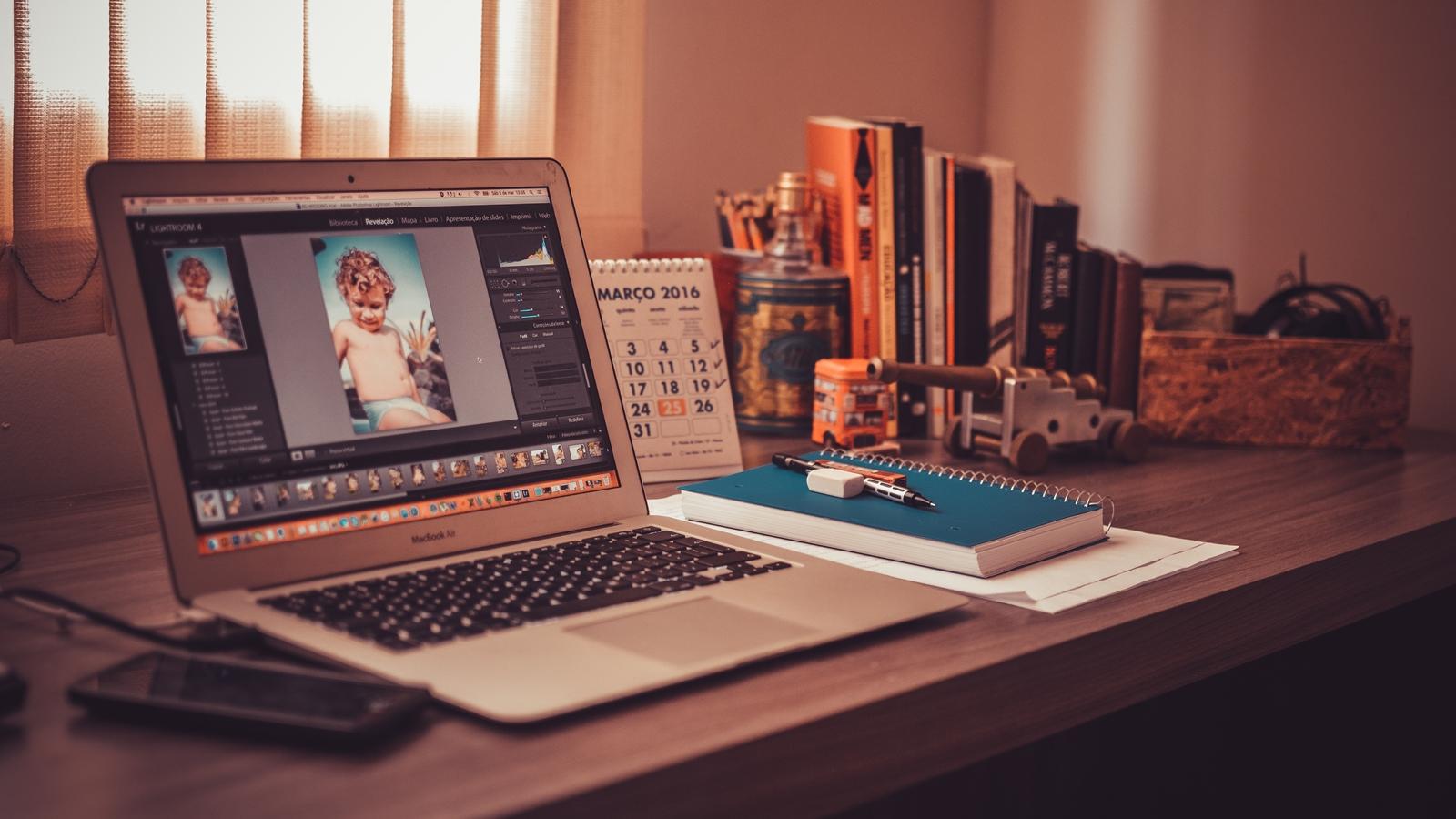 Photoshop auf einem Macbook Air auf einem Tisch mit Schreibtischutensilien