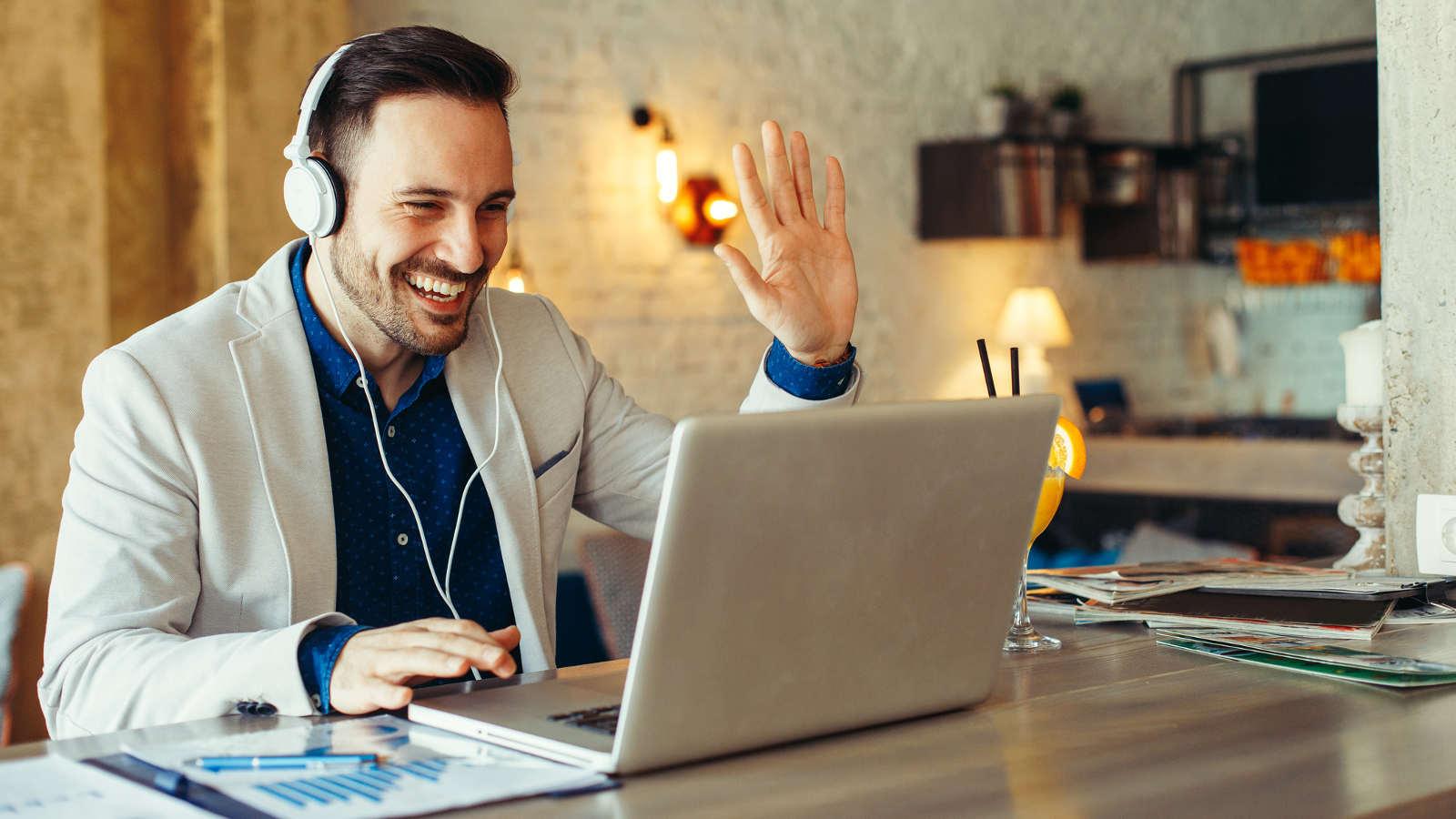 Mann nutzt Skype-Videochat am Laptop