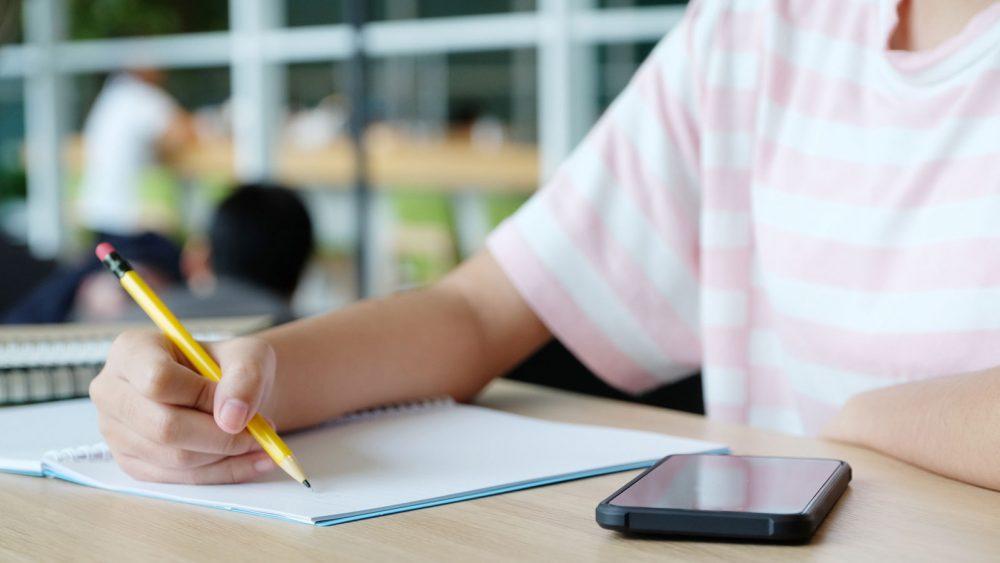 Schüler macht sich handschriftliche Notizen und nutzt das Smartphone