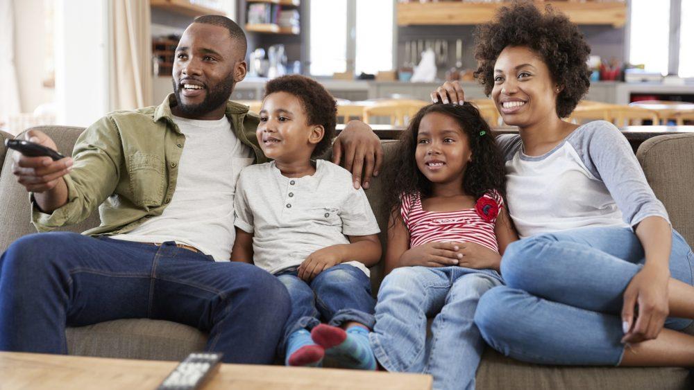 Familie sitzt auf Sofa und genießt Entertainment via Fernseher und PlayStation