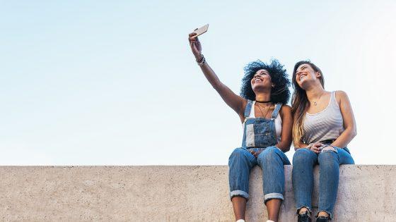 Zwei junge Frauen machen Selfie mit dem iPhone und wollen es per Mail-Anhang versenden