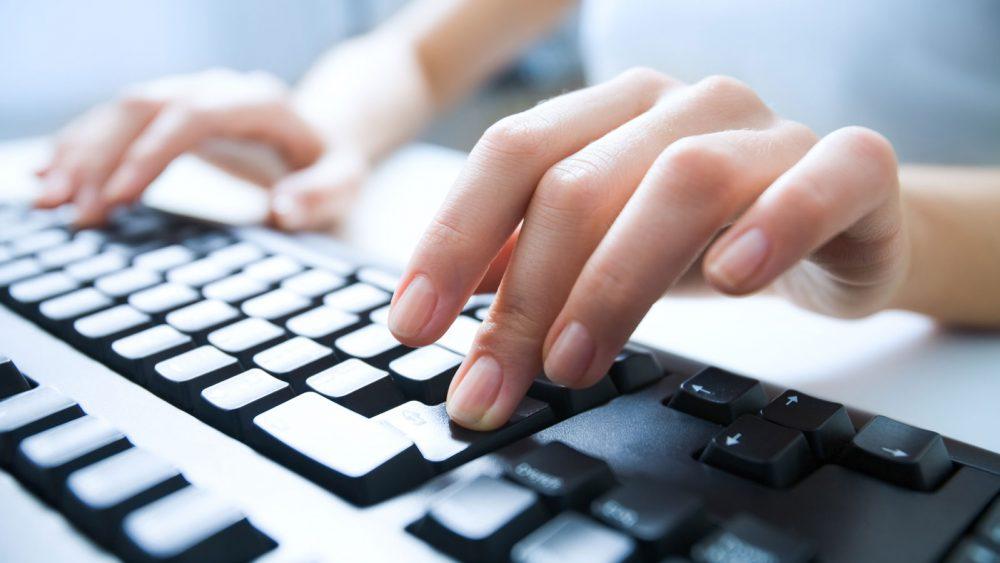 Windows-Tastatur mit Hand, ein Finger drückt die Return-Taste