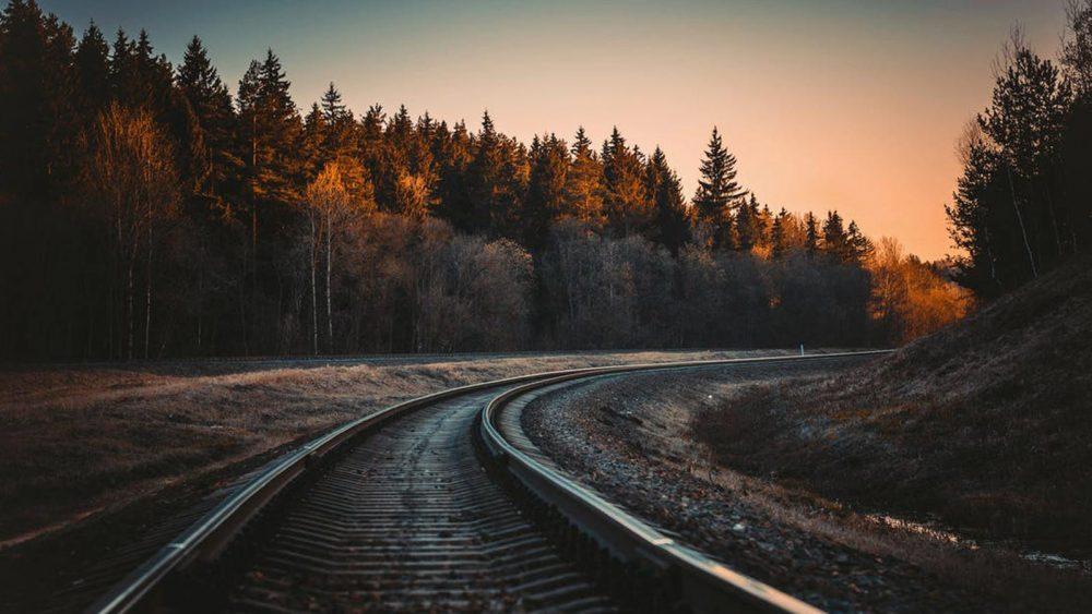 Bahn-Schinen führen in einer Rechtskurve in den Sonnenuntergang. Drum herum sind Bäume.
