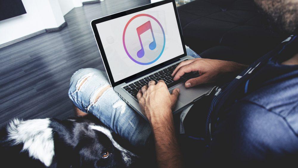 Junger Mann öffnet iTunes nach dem Back-up auf seinem MacBook