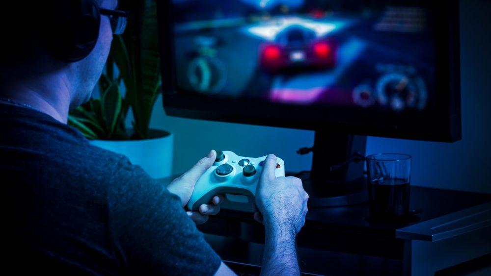 Mann spielt am PC mit einem Xbox-Controller ein Rennauto-Spiel