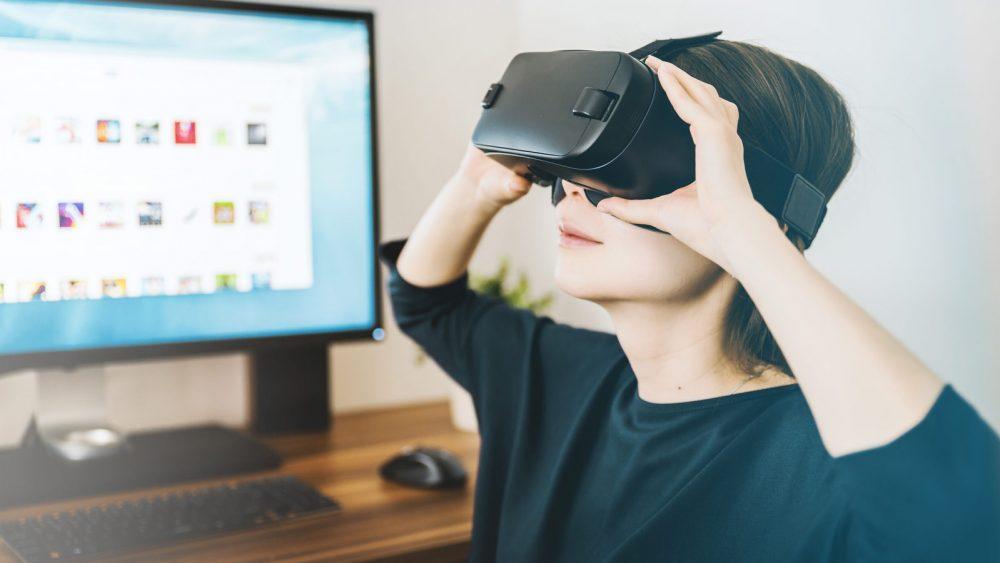 Frau mit VR Brille sitzt vor PC