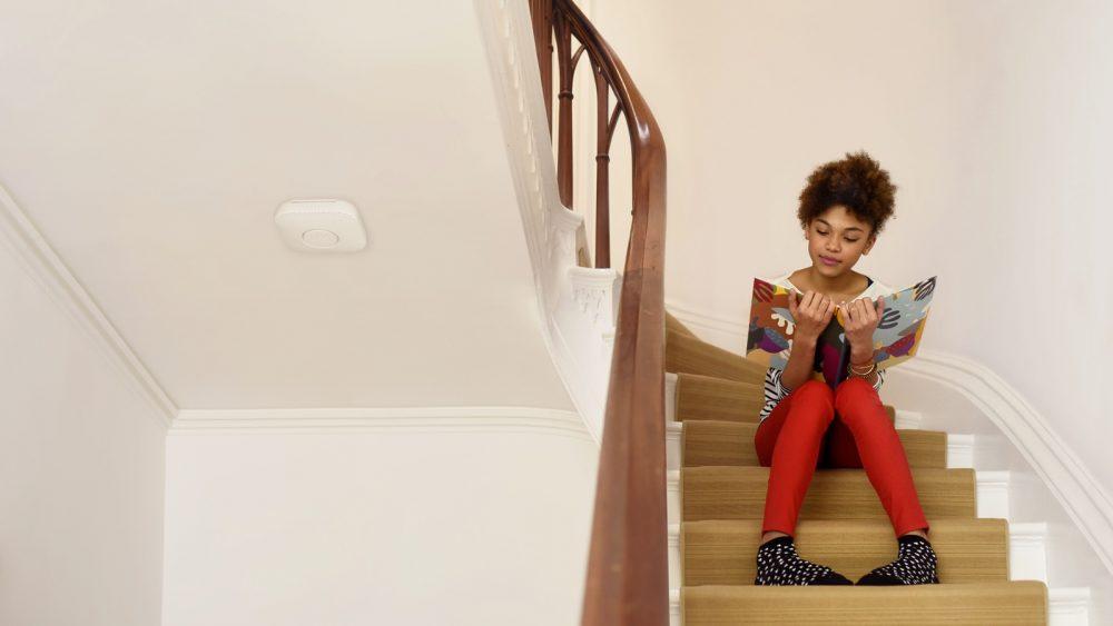 Kind sitzt auf Treppe im Flur mit Rauchmelder