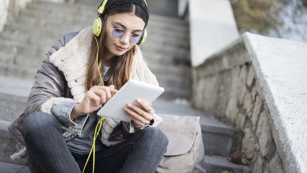 Junges Mädchen ergänzt auf Tablet Songs für gemeinsame Spotify-Playlist