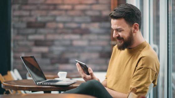 Junger Mann nutzt im Café den Google Authenticator auf mehreren Geräten