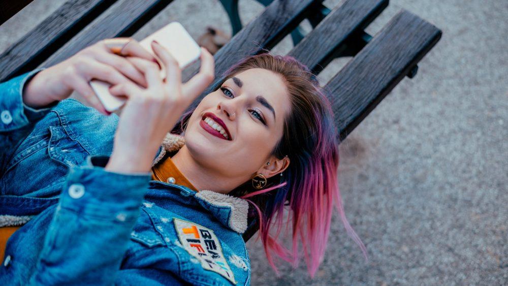 Junge Frau auf der Parkbank kontrolliert auf dem Smartphone die Klingeltöne jedes Kontakts