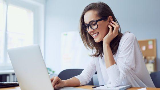 Windows 10 Sprache ändern: Frau sitzt am Laptop und lächelt