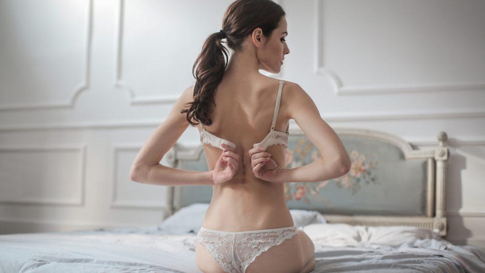 Frau sitzt auf einem Bett und schließt ihren BH