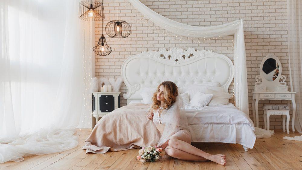 Frau bei einem Boudoir-Shooting in einem hellen Zimmer mit weißem Himmelbett