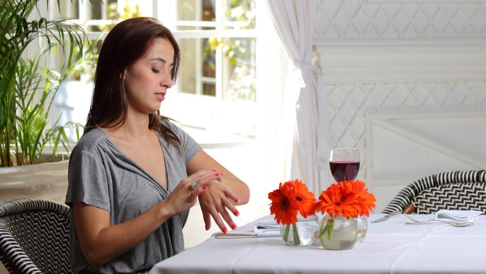 Junge Frau sitzt wartend im Restaurant und schaut auf die Uhr